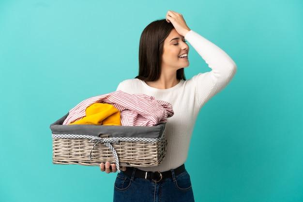Nastolatka brazylijska dziewczyna trzymająca kosz na ubrania na białym tle na niebieskim tle uświadomiła sobie coś i zamierza znaleźć rozwiązanie intend