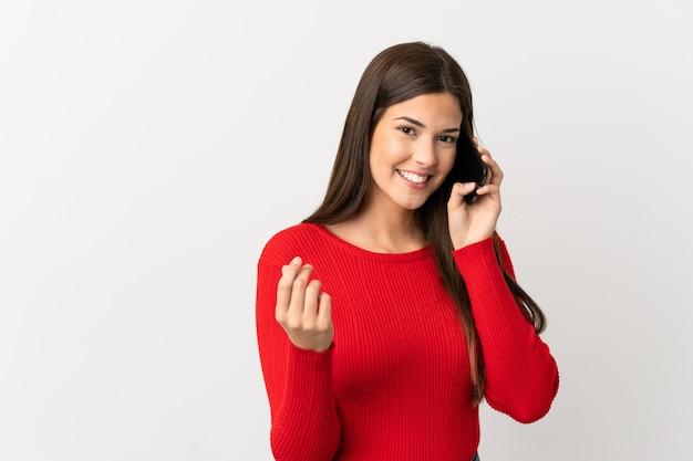 Nastolatka brazylijska dziewczyna za pomocą telefonu komórkowego na pojedyncze białe tło zarabianie pieniędzy gest