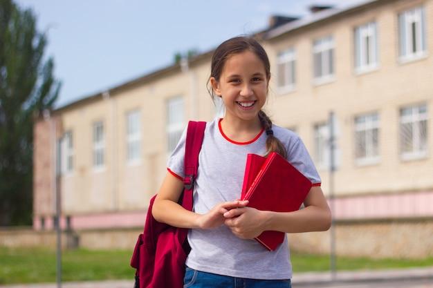 Nastolatka brunett stoi przed szkołą trzymając w rękach książki powrót do koncepcji szkoły