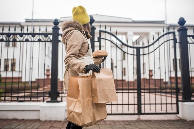 Nastolatka dostarcza artykuły spożywcze starszej osobie w czasie epidemii koronowirusa.