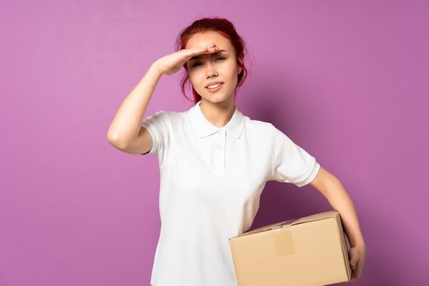 Nastolatka dostawy dziewczyna odizolowywająca na purpurowy patrzeć daleko od ręką patrzeć coś