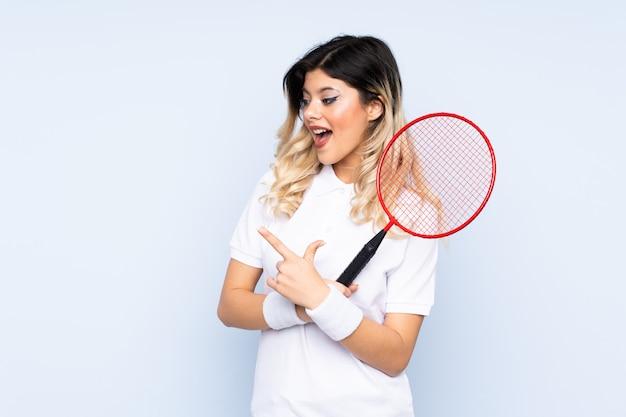 Nastolatka dziewczyny gry w badmintona na niebieską ścianą palcem wskazującym na bok