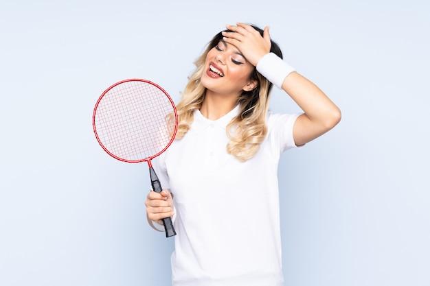 Nastolatka dziewczyny gry w badmintona na niebieską ścianą śmiejąc się