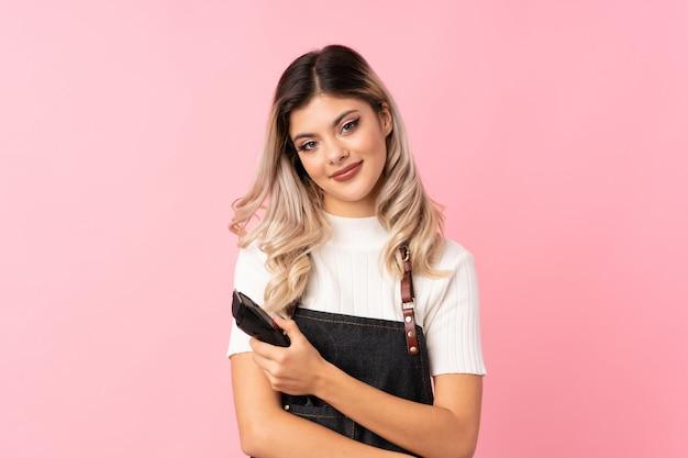 Nastolatka dziewczyny na białym tle różowy sukienka fryzjer lub fryzjer i trzymając maszynę do cięcia włosów