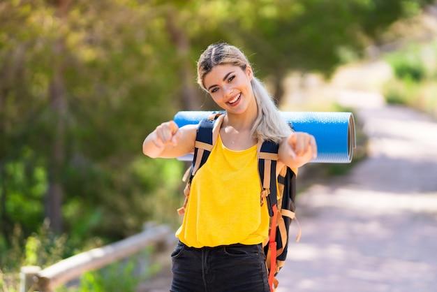 Nastolatka dziewczyny piesze wycieczki w punktach na zewnątrz palcem na ciebie podczas uśmiechania się