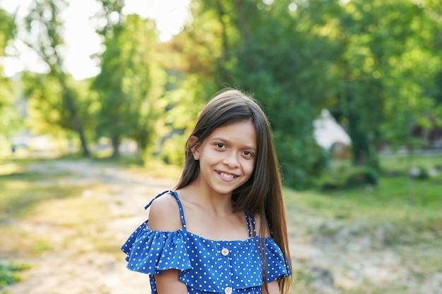 Nastolatka dziewczyny w niebieskiej sukience spacery w lesie latem o zachodzie słońca