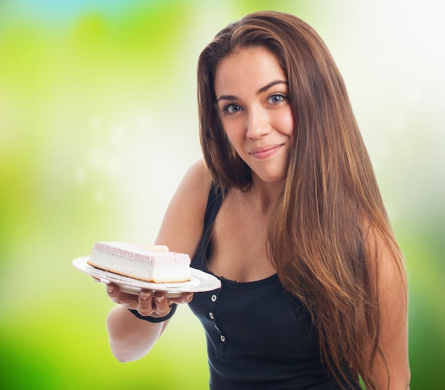 Nastolatka gospodarstwa kawałek ciasta na talerzu