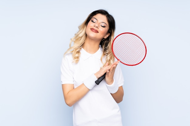 Nastolatka, grając w badmintona na niebieskiej ścianie brawo