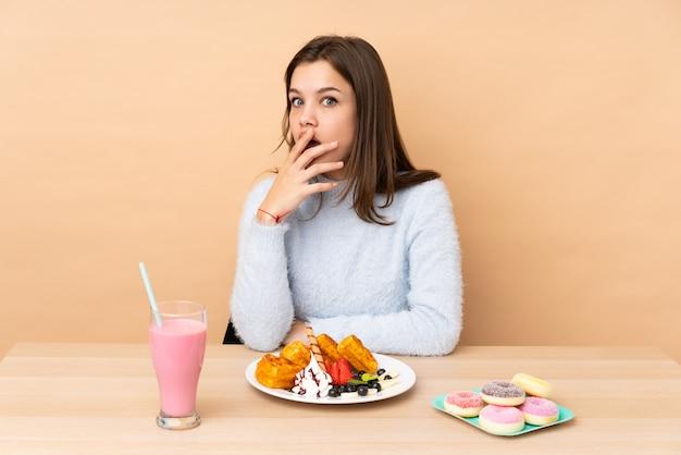 Nastolatka jedzenie gofry na beżu zaskoczony i zszokowany, patrząc w prawo