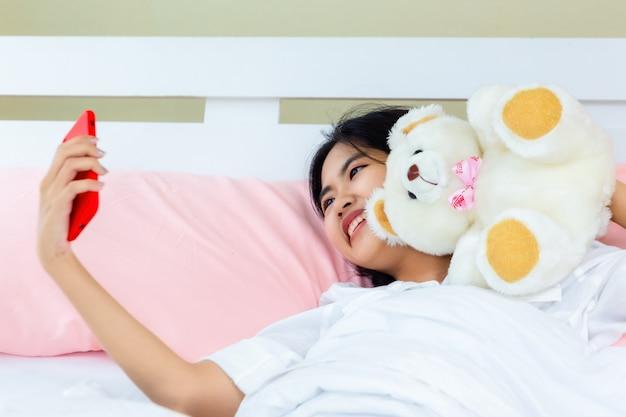 Nastolatka kobieta korzysta ze smartfona na czacie na łóżku