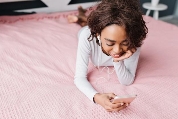 Nastolatka, ładna młoda dziewczyna leżąca na dużym różowym łóżku, słuchająca muzyki w słuchawkach, patrząc w smartfonie, pisząca z przyjaciółmi, odpoczywając w domu. nosi ładną koszulkę z długimi rękawami. widok z góry.