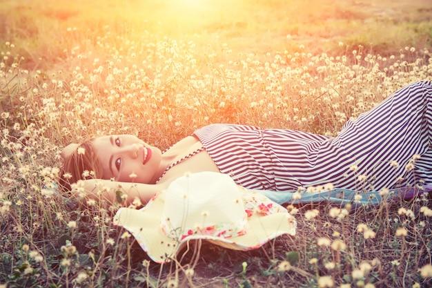 Nastolatka leżąc na łące o zachodzie słońca