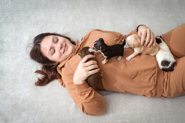 Nastolatka leży na podłodze z małymi szczeniakami pełzającymi po niej