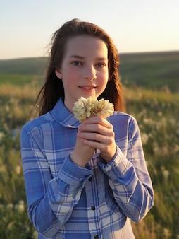 Nastolatka leży w zielonej trawie o zachodzie słońca, widok z góry, spacery i jedność z naturą