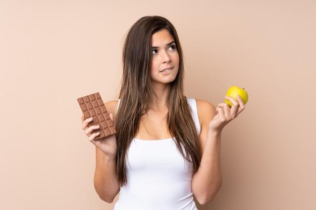 Nastolatka ma wątpliwości, biorąc tabletkę czekolady w jednej ręce i jabłko w drugiej