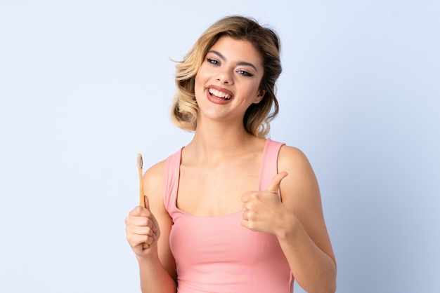 Nastolatka myje zęby na białym tle na niebieskiej ścianie z kciukami do góry, ponieważ stało się coś dobrego