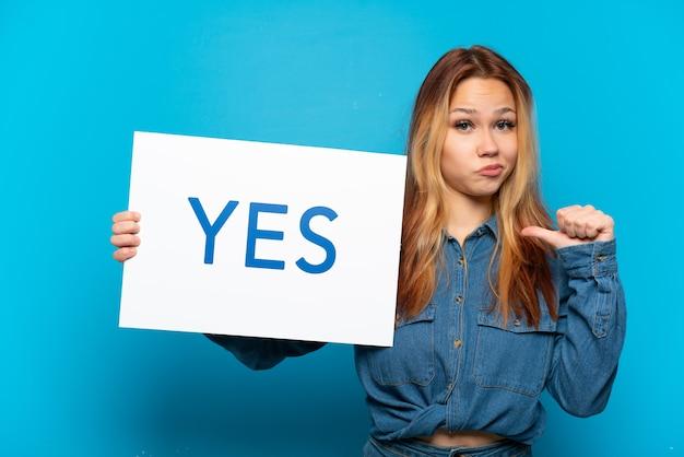 Nastolatka na białym tle trzyma afisz z tekstem tak z dumnym gestem