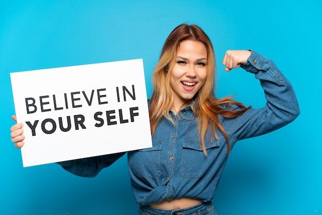 Nastolatka na odosobnionym niebieskim tle trzyma tabliczkę z tekstem wierzyć w siebie i robi silny gest