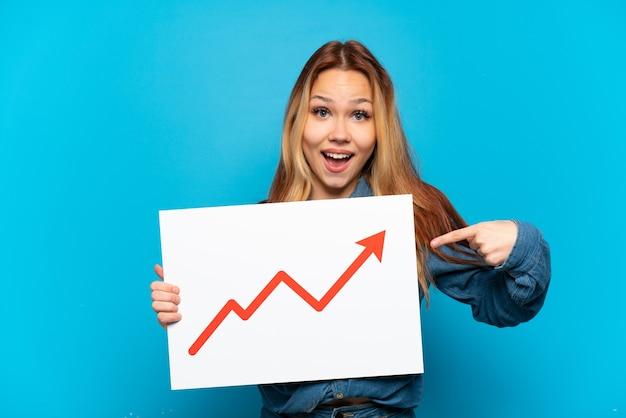 Nastolatka na odosobnionym niebieskim tle trzyma znak z rosnącym symbolem strzałki statystyki z zaskoczonym wyrazem twarzy