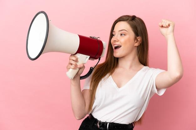 Nastolatka na różowym tle krzyczy przez megafon, aby ogłosić coś w pozycji bocznej