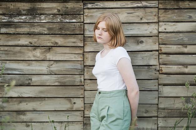 Nastolatka na starej drewnianej ścianie