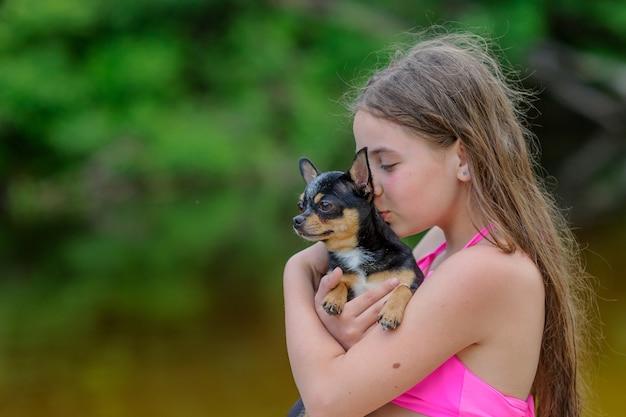 Nastolatka nad rzeką w różowych strojach kąpielowych z psem chihuahua w ramionach