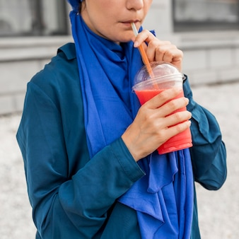 Nastolatka nosi niebieskie ubrania i pije koktajl
