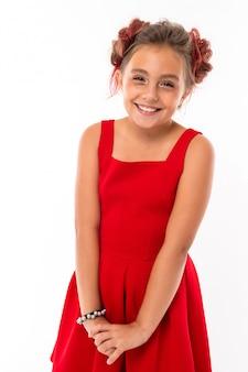 Nastolatka o długich blond włosach, różowo farbowanych końcówkach, nadziewana na dwa kępki, w czerwonej sukience, z czerwonymi słuchawkami, bransoletą, stojąca i uśmiechająca się