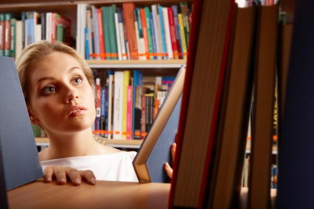 Nastolatka oddanie książek na półce
