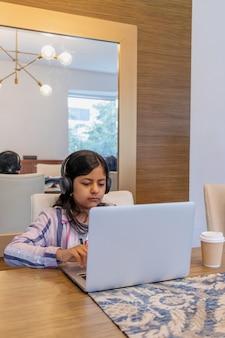Nastolatka pracuje z laptopem w salonie