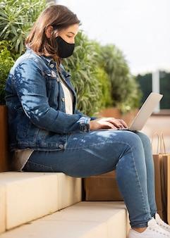 Nastolatka przegląda laptopa z maską na twarzy