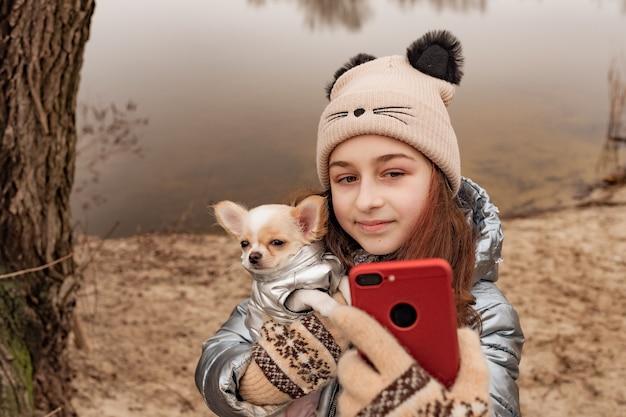 Nastolatka robi zdjęcia siebie i psa na smartfonie