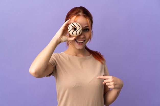 Nastolatka rosjanka na białym tle na fioletowej ścianie trzyma pączka i szczęśliwa