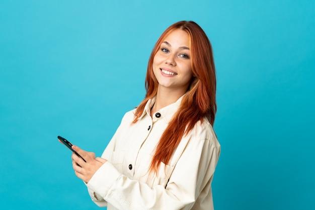 Nastolatka rosjanka na białym tle na niebieskiej ścianie, wysyłając wiadomość lub e-mail z telefonu komórkowego