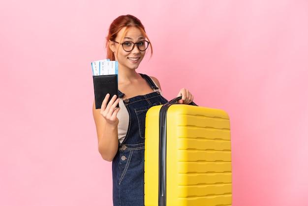 Nastolatka rosjanka na białym tle na różowej ścianie w wakacje z walizką i paszportem