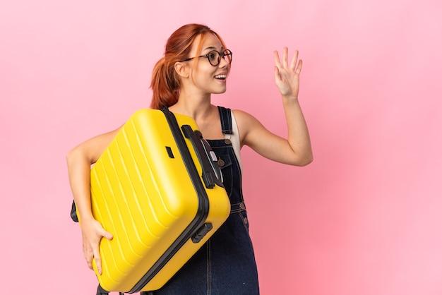 Nastolatka rosjanka na białym tle na różowej ścianie w wakacje z walizką podróżną i pozdrawiając