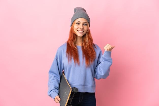 Nastolatka rosjanka na białym tle na różowej ścianie ze skate i wskazując w bok