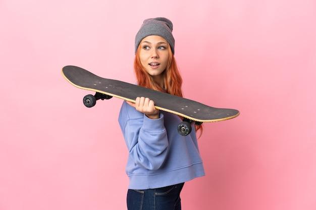 Nastolatka rosjanka na białym tle na różowej ścianie ze skate z szczęśliwy wyraz