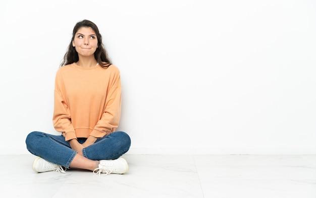 Nastolatka rosjanka siedzi na podłodze i ma wątpliwości, patrząc w górę