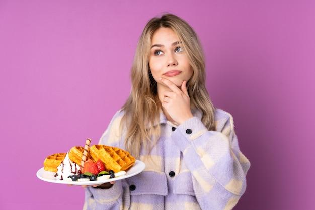 Nastolatka rosjanka trzyma gofry na białym tle na fioletowej ścianie, mając wątpliwości iz niejasnym wyrazem twarzy