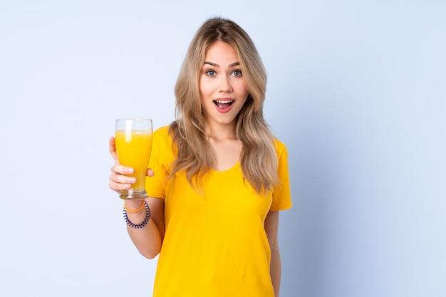 Nastolatka rosjanka trzyma sok pomarańczowy na białym tle na niebieskiej ścianie z zaskoczeniem i zszokowanym wyrazem twarzy