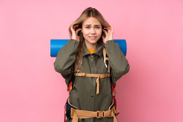 Nastolatka rosyjska alpinistka z dużym plecakiem na różowej ścianie sfrustrowana i zakrywająca uszy
