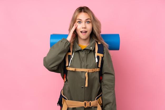 Nastolatka rosyjska alpinistka z dużym plecakiem na różowej ścianie z zaskoczeniem i zszokowaną miną