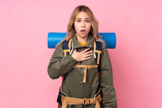 Nastolatka rosyjska alpinistka z dużym plecakiem na różowym tle zaskoczona i zszokowana, patrząc dobrze
