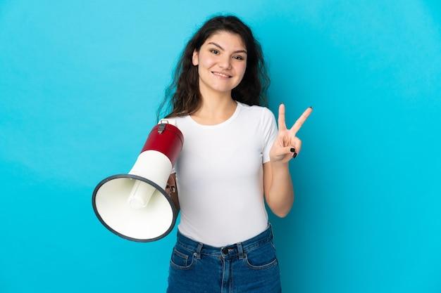 Nastolatka rosyjska dziewczyna na białym tle na niebieskim tle trzymająca megafon i uśmiechająca się i pokazująca znak zwycięstwa