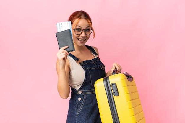 Nastolatka rosyjska dziewczyna na białym tle na różowym tle na wakacjach z walizką i paszportem