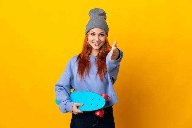 Nastolatka rosyjska skater dziewczyna na białym tle na żółtej ścianie, ściskając ręce za zamknięcie dużo
