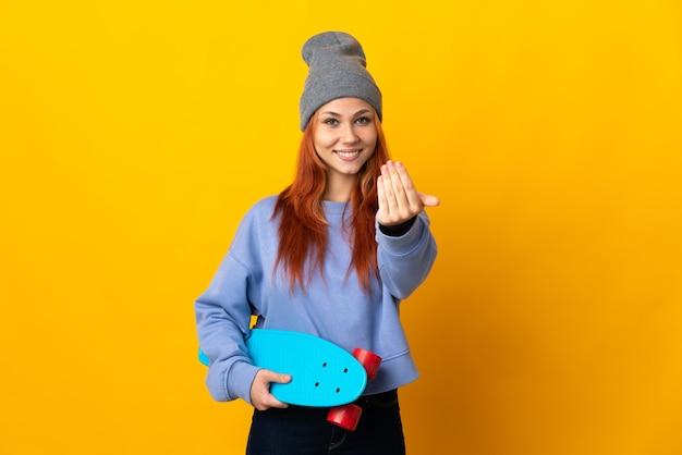 Nastolatka rosyjska skater dziewczyna na białym tle na żółtej ścianie, zapraszając do przyjścia z ręką. cieszę się, że przyszedłeś