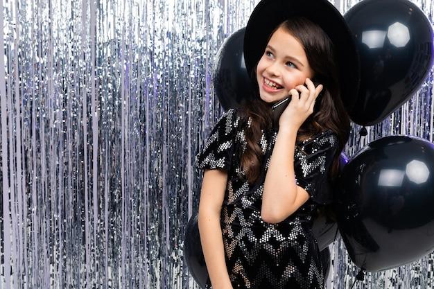 Nastolatka rozmawia przez telefon na imprezie wśród czarnych balonów helowych i świecidełka z miejsca na kopię.