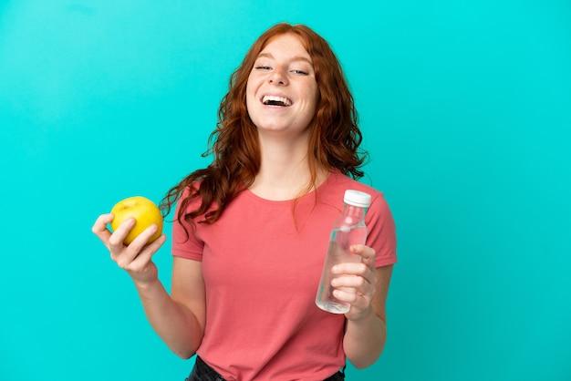 Nastolatka ruda dziewczyna na białym tle na niebieskim tle z jabłkiem i butelką wody